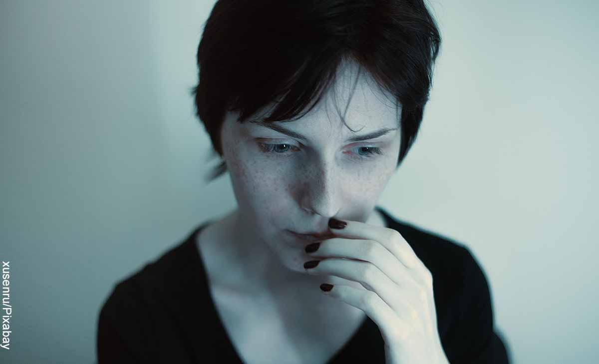 Foto de una mujer con cara preocupada que revela lo que es soñar con caída de cabello