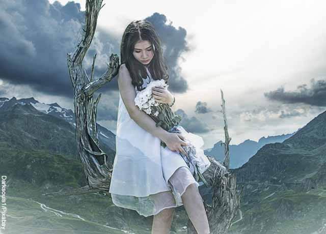 Foto de una mujer sosteniendo flores blancas entre sus manos con un paisaje de fondo
