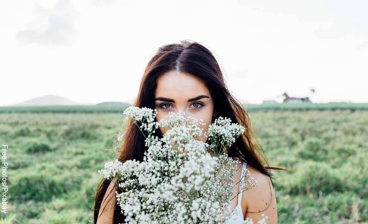Foto de una mujer con flores en sus manos que revela lo que significa soñar con flores blancas