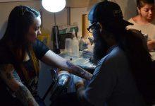 Foto de un tatuador haciendo un diseño que revela los tatuajes de relojes y su significado