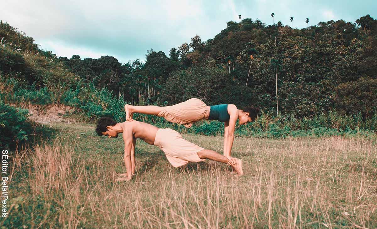 Foto de una pareja parada de manos en un paisaje que muestra el yoga en pareja