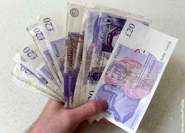 Foto de una persona con varios billetes en la mano