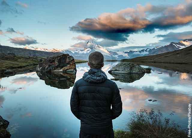 Foto de un hombre parado frente a un lago