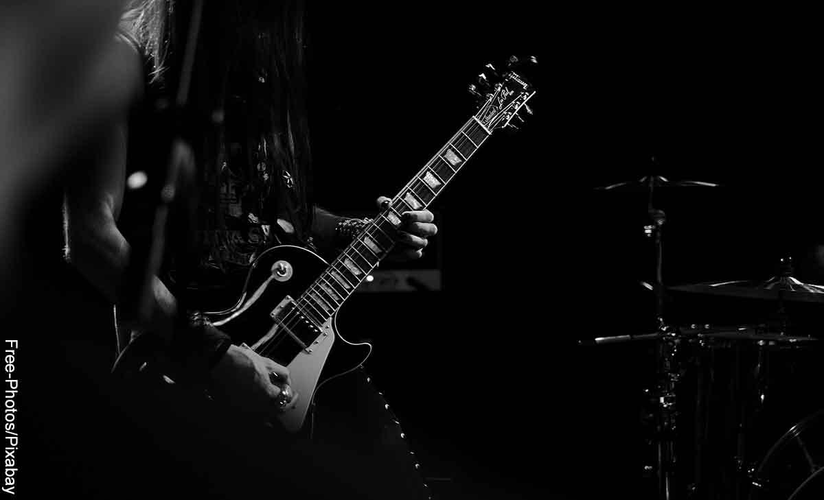 Foto de un músico tocando la guitarra eléctrica que revela las canciones de rock para dedicar