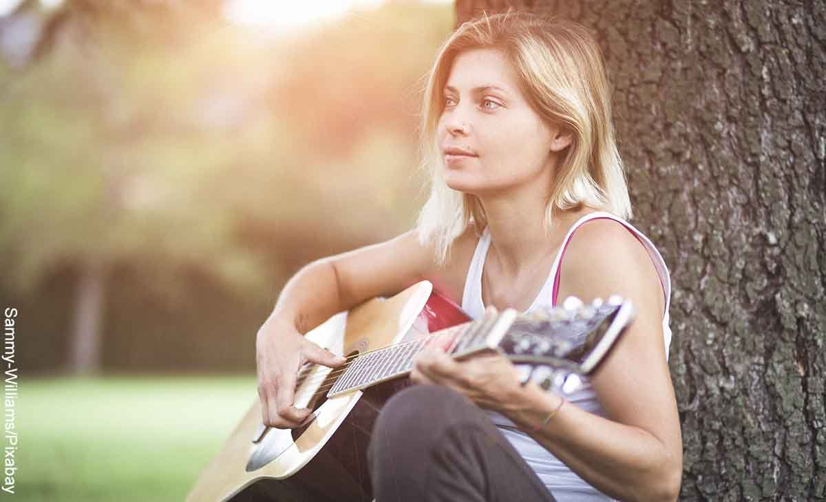 Foto de una mujer tocando la guitarra que revela las canciones para dedicar a alguien que me gusta