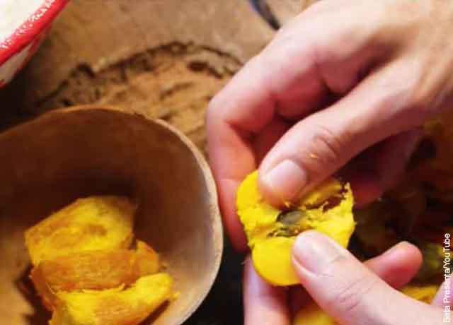 Foto de una mano pelando un chontaduro