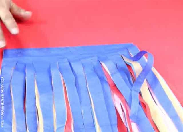 Foto de tiras de papel de colores cortadas que revelan cómo hacer pompones de colores