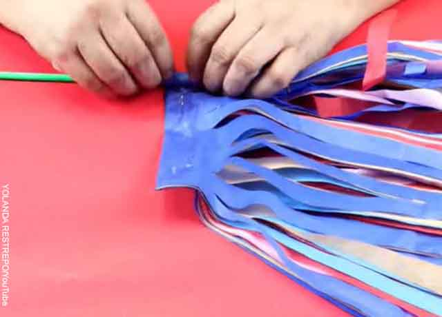 Foto de una persona pegando un pitillo a papeles de colores