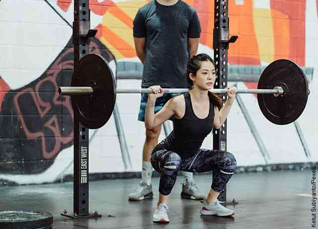 Foto de una mujer agachada levantando pesas