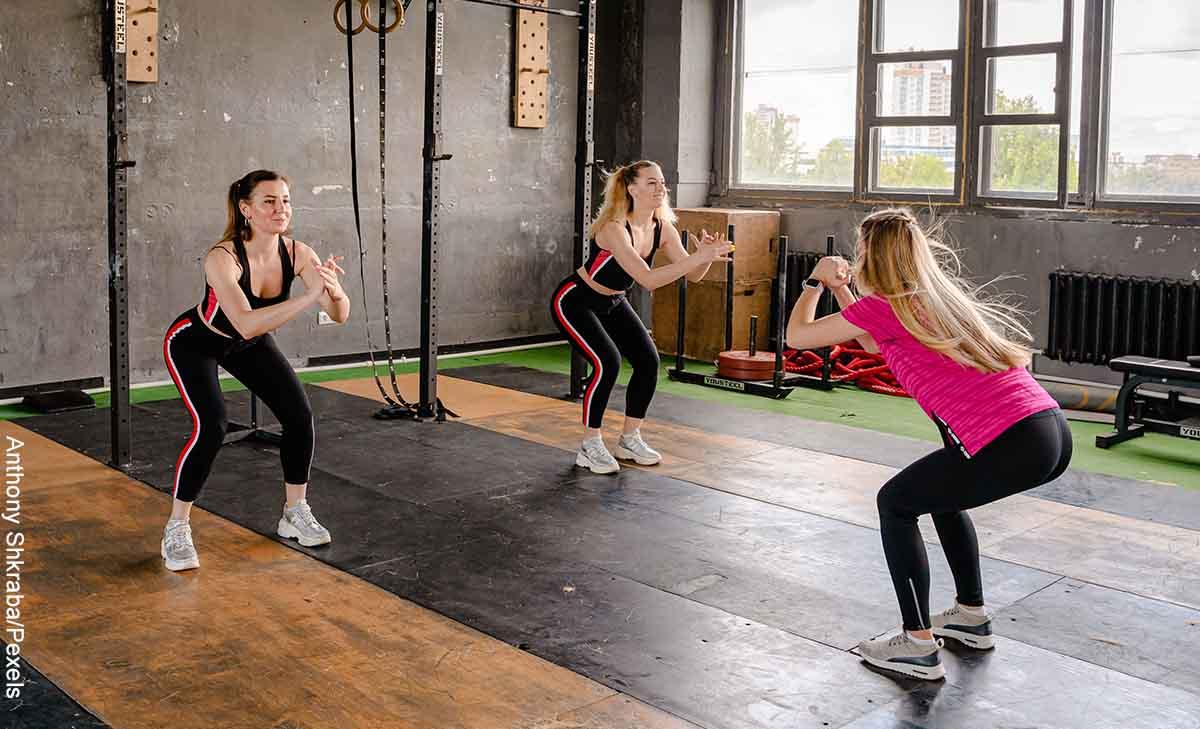 Foto de tres mujeres haciendo ejercicio que revela cómo hacer sentadillas