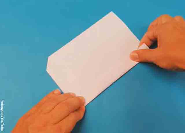 Foto de unas manos doblando un rectángulo de papel