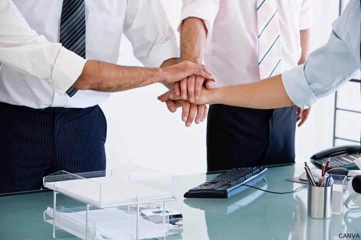 Hombres juntando sus manos en una oficina para celebrar un triunfo laboral
