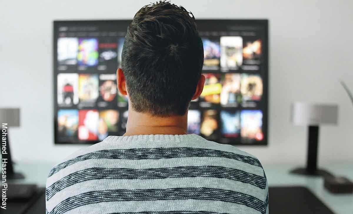 Foto de un hombre sentado frente a su tv que muestra las mejores películas de todos los tiempos