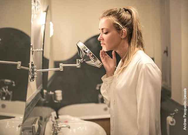 Foto de una joven viendo su rostro al espejo en el baño