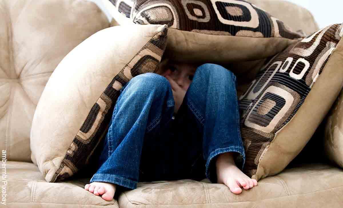 Foto de un niño debajo de almohadas que revela las mejores películas de miedo
