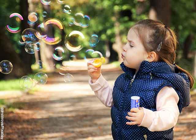 Foto de una niña haciendo burbujas en el parque