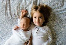 Foto de una bebé junto con su hermana acostada en la cama que muestra los nombres de niñas con significado