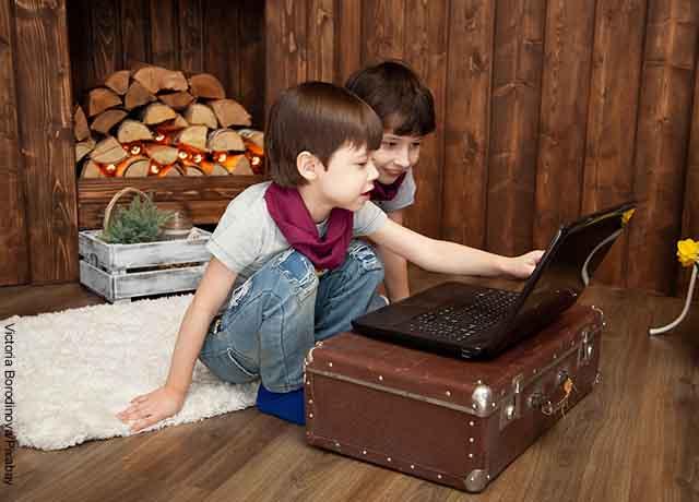 Foto de dos niños jugando en un computador que muestra las páginas para ver películas gratis