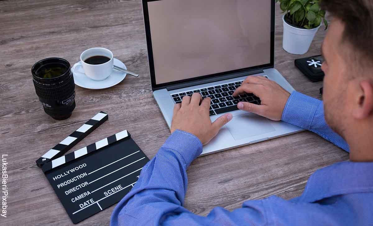 Foto de un hombre sentado frente a su computador que revela las páginas para ver películas gratis