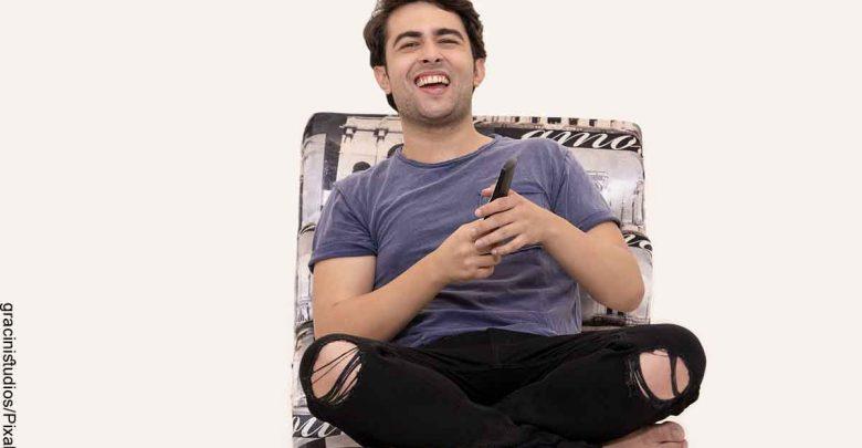 Foto de un hombre riendo con un control remoto que revela las películas colombianas de comedia