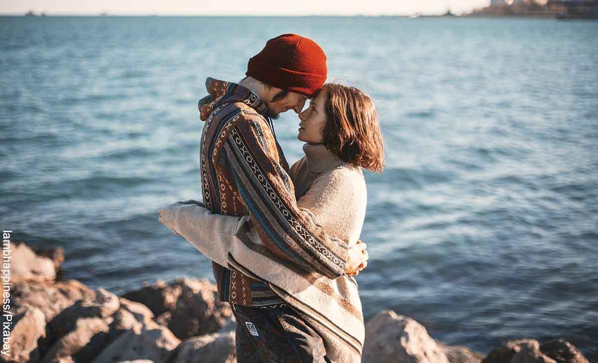 Foto de una pareja abrazada frente al mar que muestra las películas de comedia romántica