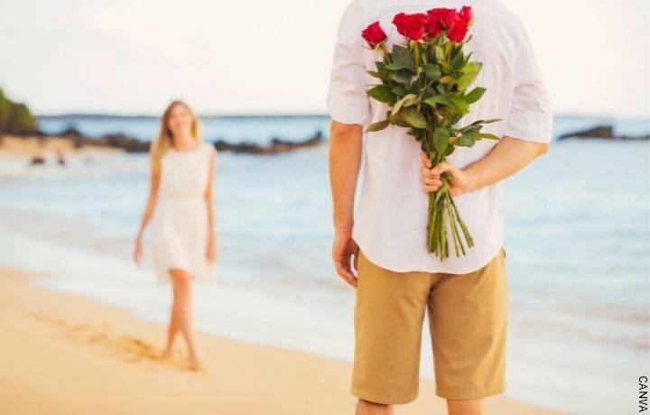 Foto de una pareja en la playa con rosas rojas