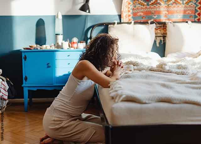 Foto de una mujer orando al lado de su cama