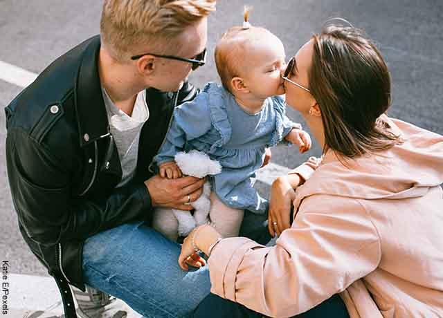 Foto de una pareja besando a su hijo