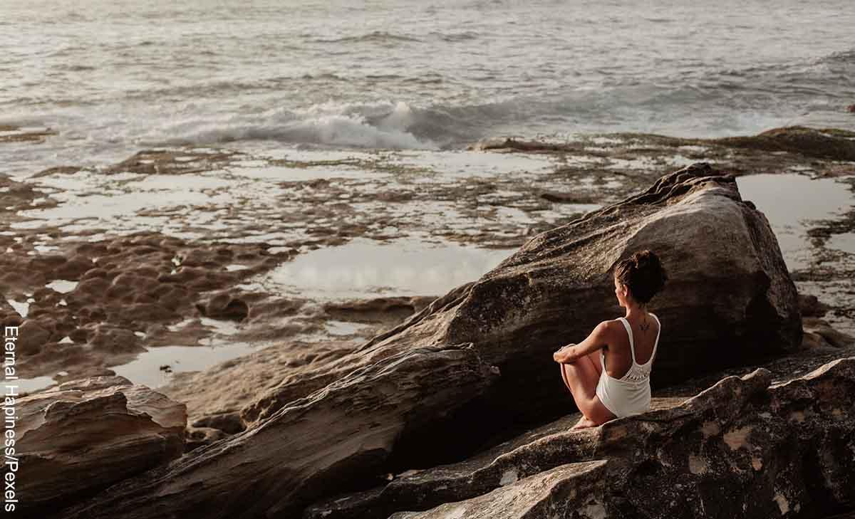 Foto de una mujer meditando frente al mar que revela qué significa 10 10