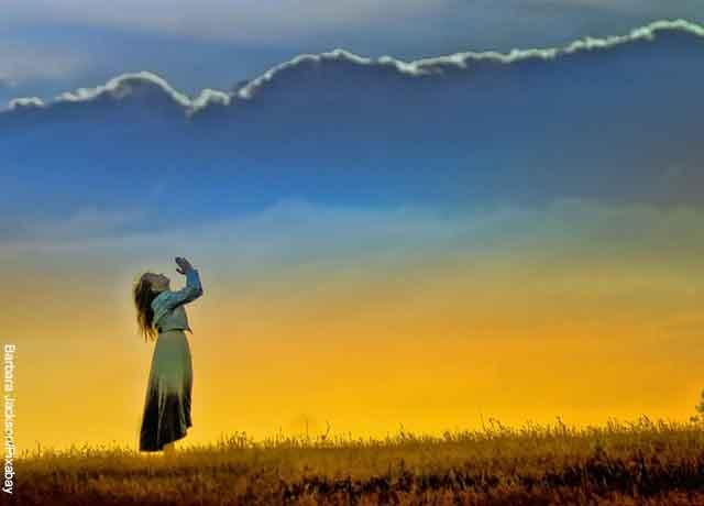 Foto de una mujer orando en un campo abierto