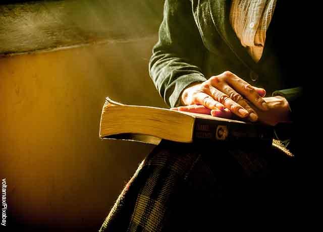 Foto de una mujer sentada con una biblia sobre sus piernas