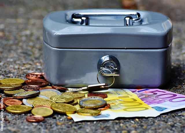 Foto de billetes y monedas afuera de cofre