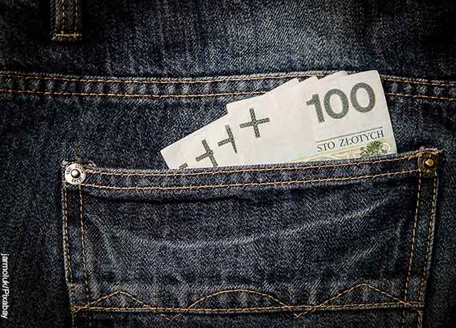 Foto de unos billetes en un bolsillo que revelan qué significa soñar con encontrar dinero