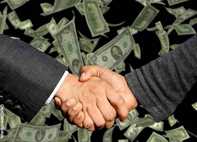 Foto de dos personas dándose la mano con billetes al fondo