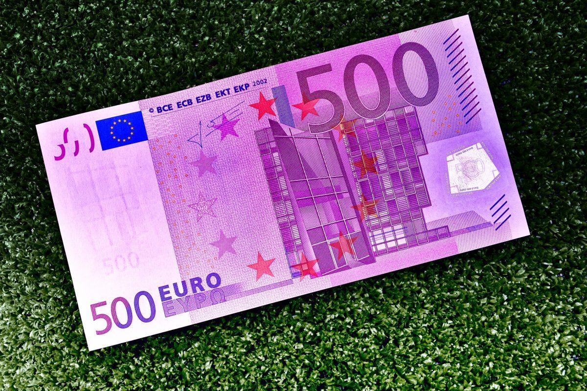 Foto de un billete tirado en el pasto que muestra qué significa soñar con encontrar dinero