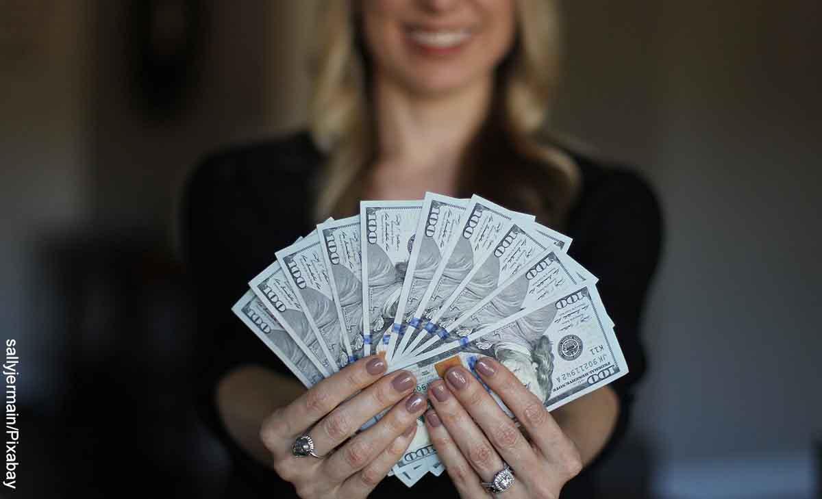 Foto de una mujer sonriendo con billetes en la mano que revela qué significa soñar con encontrar dinero