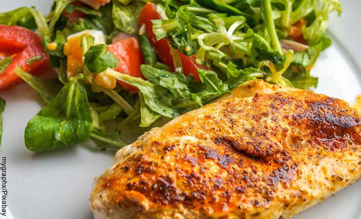 Foto de un filete de pechuga y una ensalada que revela las recetas fáciles con pechuga de pollo