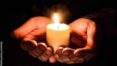 Foto de una persona sosteniendo una vela que muestra el significado de la llama de las velas