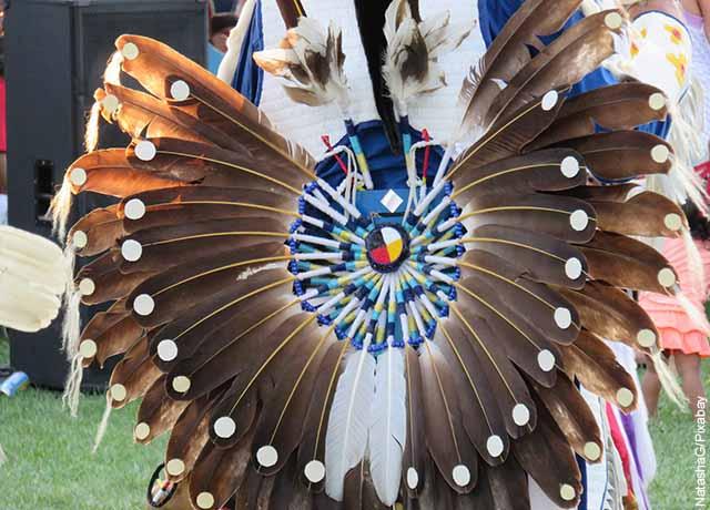 Foto del traje de un indígena con plumas cafés