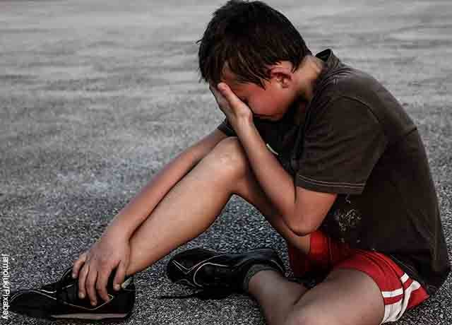 Foto de un niño lastimado llorando en el piso