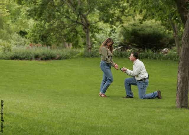 Foto de un hombre arrodillado frente a una mujer en el parque