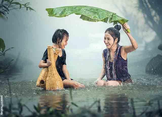 Foto de una niña y una mujer bajo la lluvia en un río