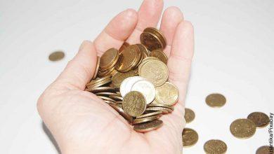 Foto de una persona con muchas monedas que revela lo que significa soñar con monedas en la mano