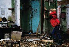 Foto de una mujer cerrando una puerta en casa que revela las mejores películas de terror